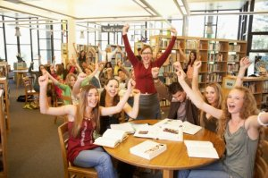 Group of teenagers with teacher cheering in library